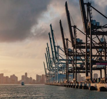 Aerial view of cranes in the Port of Miami with the Miami skyline in the background