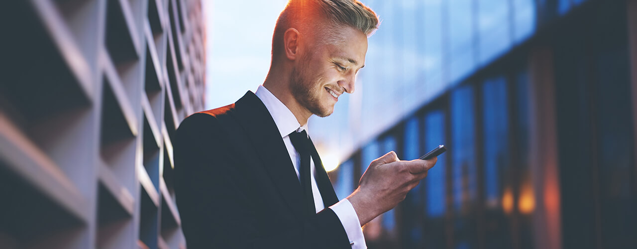 A businessman looking into his smartphone in front of an office building