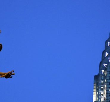 view of top of chrysler building in new york city and statue of mercury on grand central terminal