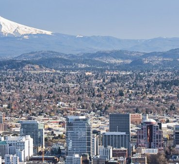 A wide shot of the skyline of Portland, OR with Mount Hood in the background