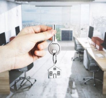 broker hand holding out key to turnkey office space